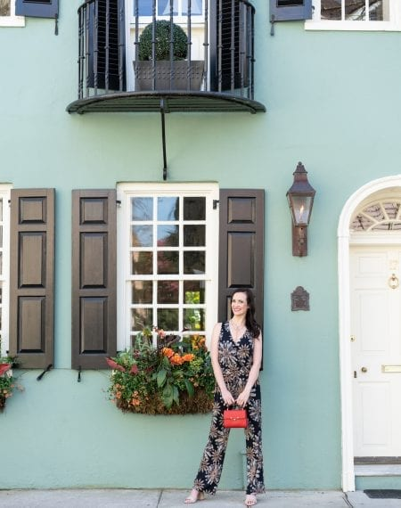 Life With Ashley T standing in front of a turquoise house in downtown Charleston in a jumpsuit